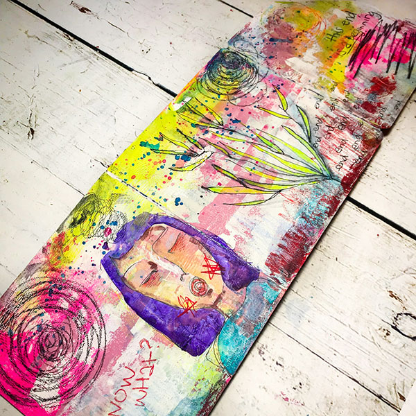 altered board book with colourful art journaling showing a feminine face with eyes closed